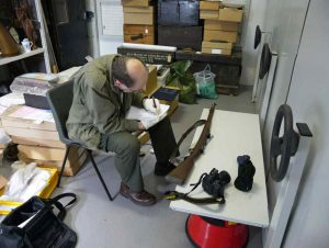 Image: Guy Wilson cataloging part of the firearms collection